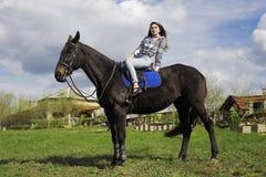 女孩在马背上走本质上在一匹黑马 库存照片