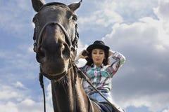 女孩在马背上走本质上在一匹黑马 免版税库存图片