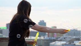 女孩在高大厦的屋顶花费 有长的头发的女孩开始在大厦屋顶的泡影 可爱 影视素材