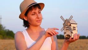 女孩在麦田在她的手上站立并且拿着一台玩具风车 女孩慢慢地转动风车 概念  股票录像