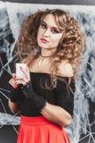 女孩在黑墙壁前面的巫婆在一条女衬衫和红色裙子为与蜡烛的万圣夜 库存照片