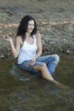 女孩在水中投掷石头 免版税库存照片