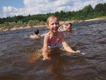 女孩在水中游泳 库存图片