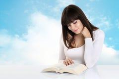 女孩在读吸收了书在与天空云彩的背景 库存图片