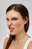 女孩在嘴和鬼脸画象有香烟的在面孔的 库存照片