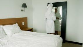 女孩在浴巾的镜子前站立 股票录像
