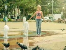 女孩在寻找喷水的喷泉的一个热的夏日在城市 库存图片