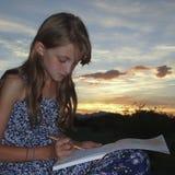 女孩在素描便笺簿画 免版税库存图片