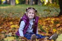 女孩在晴朗的秋天公园坐叶子 免版税库存图片