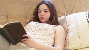 女孩在轻松的沙发读畅销书书 股票录像
