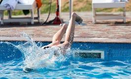 女孩在水池潜水 免版税库存图片