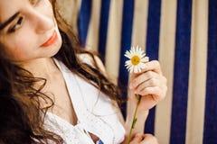 女孩在他的手上的拿着一朵雏菊在一个夏日 库存照片