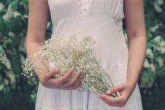 女孩在他们的手上的拿着花 库存图片