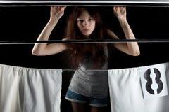 女孩在黑背景的窗口里与白色帷幕 免版税图库摄影