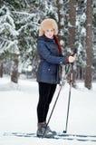 女孩在滑雪的冬天森林里 图库摄影
