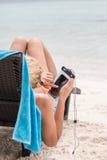 女孩在sunbed说谎并且观看某事在她的电话 库存图片