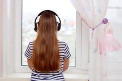 女孩在w听到与耳机的音乐并且看 免版税库存照片