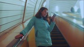 女孩地下地铁的生活方式少年在自动扶梯乘坐,拿着智能手机 女孩深色的女儿 影视素材