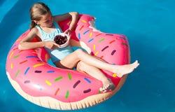 女孩坐一个五颜六色的可膨胀的多福饼用樱桃 库存照片