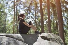 女孩坐一个大岩石在森林夏天晴天 Botto 库存图片