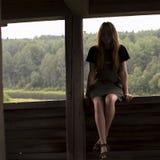 女孩坐一个木眺望台的栏杆 免版税库存图片