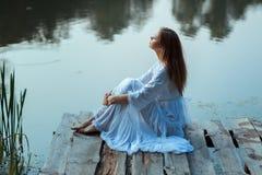 女孩坐一个木码头和梦想 免版税库存照片
