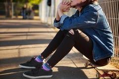 女孩坐一个滑板在公园 免版税库存图片