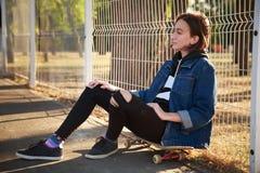 女孩坐一个滑板在公园 图库摄影
