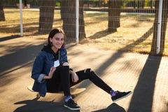 女孩坐一个滑板在公园 库存图片