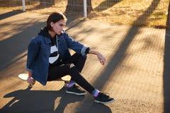 女孩坐一个滑板在公园 库存照片