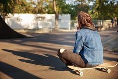 女孩坐一个滑板在公园 免版税图库摄影