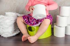 女孩坐一个绿色罐并且学会基础卫生 库存照片