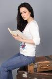 女孩坐一个老手提箱和读书 免版税图库摄影
