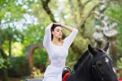 女孩坐一匹马在公园 库存图片