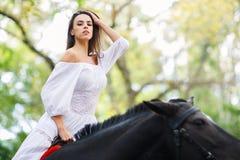 女孩坐一匹黑马 外面 免版税库存照片