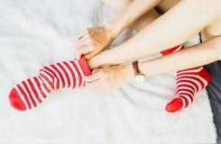 女孩坐一张白色地毯并且投入了袜子,白色加标点红色边 库存图片