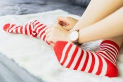 女孩坐一张白色地毯并且投入了袜子,白色加标点红色边 免版税库存图片