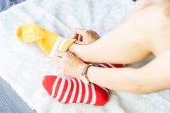 女孩坐一张白色地毯并且投入了袜子,黄色加标点红色边 免版税库存照片