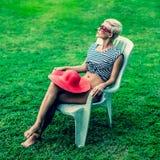 女孩坐一把椅子在公园 库存图片
