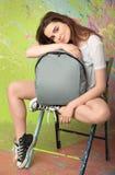 女孩坐一把椅子在演播室 免版税库存图片