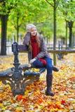 女孩坐一条长凳在公园在一秋天天 免版税图库摄影