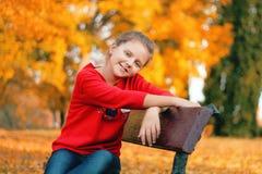 女孩坐一条长凳在公园 图库摄影