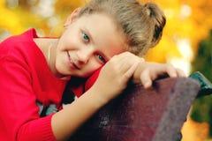 女孩坐一条长凳在公园 库存图片