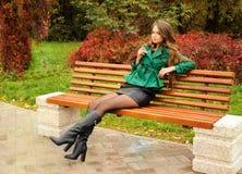 女孩坐一条长凳在公园 库存照片
