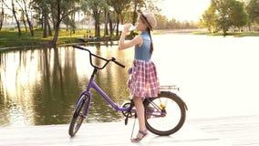 女孩坐一辆淡紫色自行车靠近河在日落和饮用水从一个透明瓶 ?? 影视素材