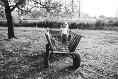 女孩坐一辆老木无盖货车在村庄 图库摄影