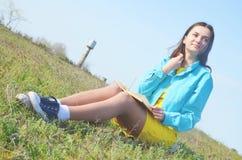 女孩坐与书的领域在夏天 免版税图库摄影