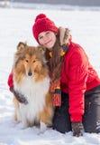 女孩坐与大牧羊犬狗的雪 库存照片