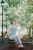 女孩坐与樱花小树枝的一条长凳  免版税库存照片