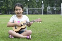 女孩坐与演奏尤克里里琴的快乐的微笑的草 免版税库存图片